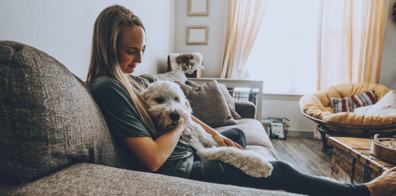 Woman and dog sitting on couch
